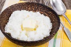 挤奶米粥用在木碗的黄油 免版税图库摄影