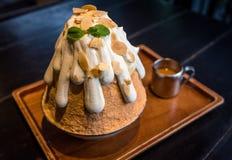 挤奶茶与甜奶油色顶部的被刮的冰在一个木盘子, 免版税库存图片