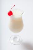 挤奶鸡尾酒用在一块高玻璃的一棵樱桃 免版税库存照片