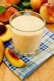 挤奶鸡尾酒用在餐巾的桃子 库存图片