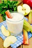 挤奶鸡尾酒用大黄和苹果在委员会 免版税库存图片