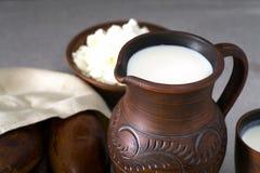挤奶,酸奶干酪,在陶器的饼 免版税库存图片