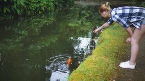 挥动一条大红色鱼的女孩在河 股票视频