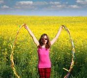 挥动与五颜六色的丝带春季的小女孩 库存图片