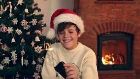 挥动与圣诞节闪烁发光物的愉快的男孩 股票录像