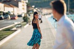 挥动与在街道上的一个人的年轻可爱的妇女 回顾在一个英俊的人的私秘微笑的妇女 女性吸引力 库存图片