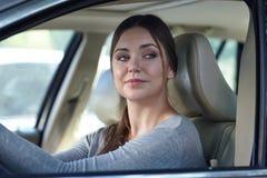 挥动与步行者或其他司机的汽车的年轻可爱的卖弄风情的白种人妇女 时髦和确信的不同的妇女是 库存照片