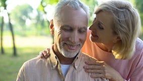 挥动与英俊的丈夫的关心的成熟妻子在公园,耳语的恭维 库存照片
