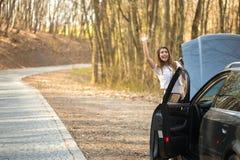 挥动为在路的帮助的美丽的少妇 免版税库存图片