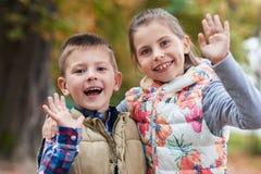 挥动你好的逗人喜爱的小孩在公园 免版税库存照片