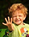 挥动入太阳的小男孩 免版税库存照片
