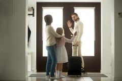 挥动再见对妻子和女儿的微笑的父亲离开在家 免版税库存图片