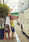 挥动再见对他们的公共汽车的朋友的年轻夫妇 图库摄影