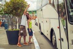 挥动再见对他们的公共汽车的朋友的年轻夫妇 免版税图库摄影