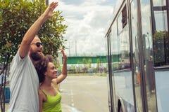 挥动再见对他们的公共汽车的朋友的年轻夫妇 库存图片