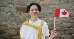 挥动加拿大旗子的十几岁的男孩画象站立户外微笑 影视素材