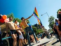 挥动同性恋自豪日旗子的小组男孩 免版税图库摄影