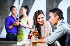 挥动和喝在夜总会酒吧的亚洲夫妇 免版税库存图片