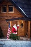 挥动和带来圣诞树的圣诞老人在房子里 免版税库存图片