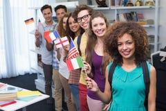 挥动国际旗子的愉快的学生 免版税库存图片