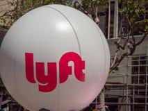 挥动在一个城市布局的大白色Lyft气球 库存图片