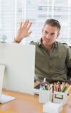 挥动在一个现代办公室的创造性的企业雇员 免版税图库摄影