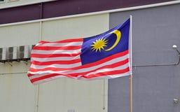 挥动在与典型的大厦的天空中的马来西亚的旗子在背景中 免版税库存图片