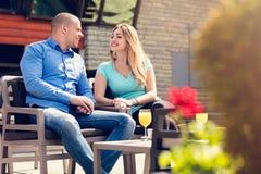 挥动在咖啡馆 坐在咖啡馆的美好的爱恋的夫妇享用在咖啡和交谈 爱,浪漫史,约会 免版税库存图片