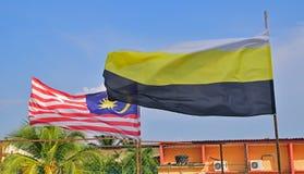 挥动在天空中的马来西亚的旗子与霹雳州状态一起旗子在前景的 免版税库存照片