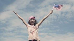 挥动在天空背景慢动作的女孩美国旗子 股票视频