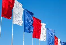 挥动在天空背景的白色,红色和蓝旗信号 免版税图库摄影