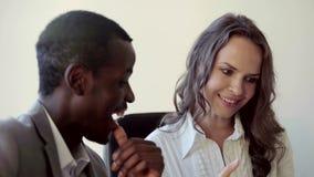 挥动在工作的两个混杂的同事 他们聊天和微笑 股票录像