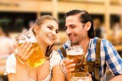 挥动在慕尼黑啤酒节啤酒帐篷的年轻夫妇,当喝啤酒时 免版税库存照片