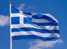 挥动在旗杆的风的希腊的旗子反对与云彩的天空在晴天 免版税图库摄影