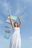 挥动在海边的女孩一条五颜六色的围巾 免版税库存图片