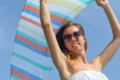 挥动在海边的女孩一条五颜六色的围巾 库存照片