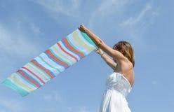 挥动在海边的女孩一条五颜六色的围巾 免版税库存照片