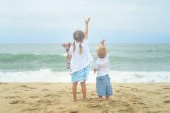 挥动在海滩的兄弟、姐妹和他们的狗 图库摄影