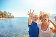 挥动在海滩的照相机的逗人喜爱的小男孩 免版税图库摄影