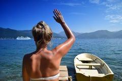 挥动在游轮的比基尼泳装的可爱的年轻金发碧眼的女人 免版税图库摄影