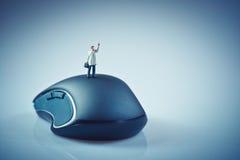 挥动在计算机老鼠顶部的微型商人 事务 免版税库存图片
