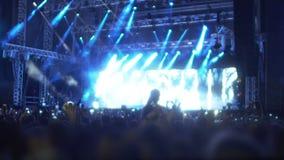 挥动在音乐会,人们的激动的观众的手享受音乐在展示 股票录像