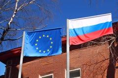 挥动在风的俄罗斯和欧盟旗子  免版税库存图片