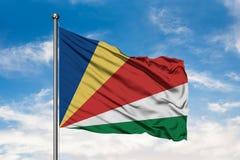 挥动在风的塞舌尔的旗子反对白色多云天空蔚蓝 塞舌尔的旗子 免版税图库摄影