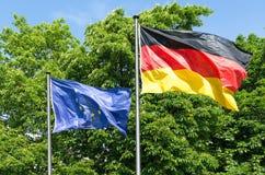 挥动在风的德国和欧洲旗子  免版税库存照片