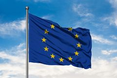 挥动在风的欧盟旗子反对白色多云天空蔚蓝 免版税库存照片