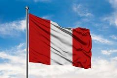 挥动在风的秘鲁的旗子反对白色多云天空蔚蓝 秘鲁旗子 免版税库存图片