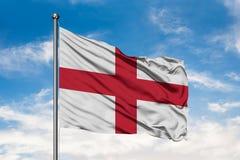 挥动在风的英国的旗子反对白色多云天空蔚蓝 英国旗子 免版税库存图片