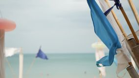 挥动在风的蓝旗信号 振翼在多云天气的风的小三角蓝旗信号在热带海滩 股票录像