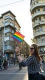 挥动在骄傲游行的愉快的女同性恋的妇女一面彩虹旗子,索非亚在街道的自豪感节日 骄傲红色顶头的太阳镜 免版税图库摄影